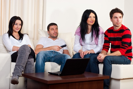 Group of four friends watching tv and sitting comfortable on couch