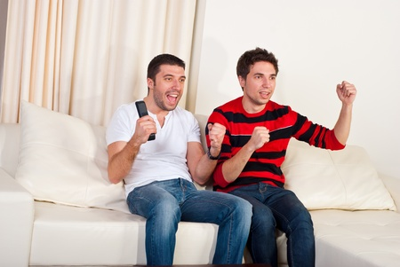 Two excited men sitting on couch and watching favorite team soccer with goal