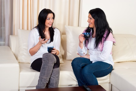 two people talking: Two friends women sitting on couch   holding cups of coffee and having conversation in a living room