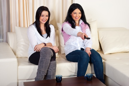 Two women friends watching tv and sitting comfortable on couch in a living room photo