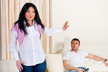 Furios couple in conflict in their living room,woman gestivculate:Talk with my hand! to her husband photo
