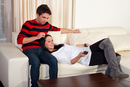Loving young couple sitting on sofa in living room photo