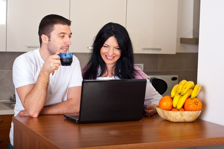 Cheerful couple drinking coffee using laptop and having funny conversation in the morning in their kitchen photo