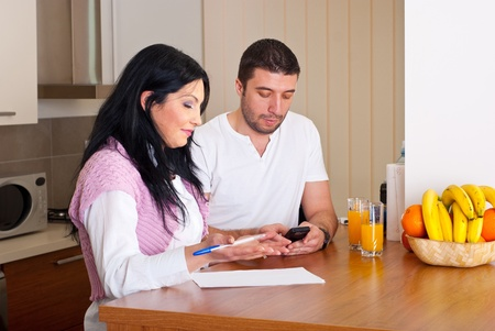 Mid adult couple calculating their expenses in their kitchen at home Stock Photo - 8902732