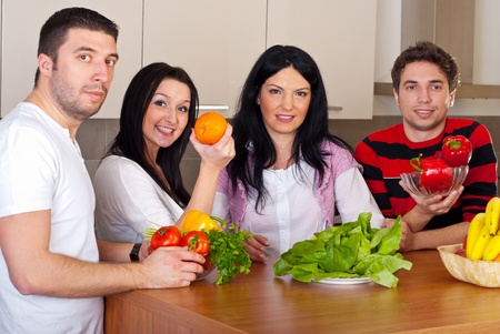 Group of four friends with fruits and vegetables in kitchen photo