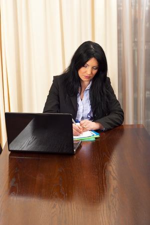 Serious business woman working and writing in her office photo