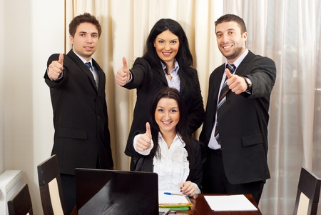 Cheerful business people giving thumbs up in a meeting room photo