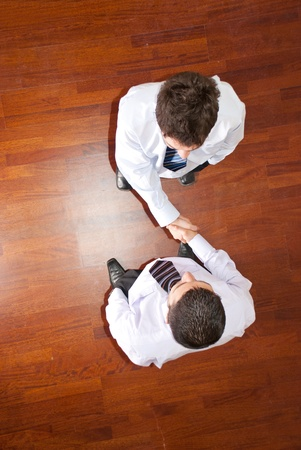 greeting people: Top view of two business men handshake  on  wooden floor