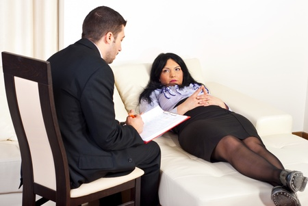 Psychiatrist giving advices to a patient woman lying on sofa photo