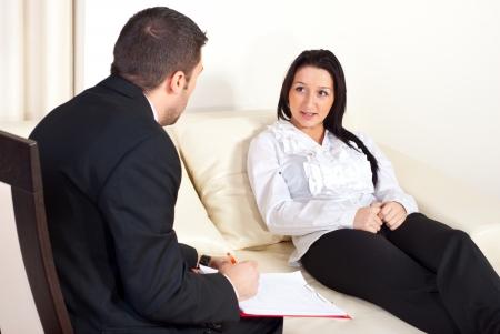 terapia psicologica: Paciente mujer sentada en un sof� y hablando con hombre psic�logo
