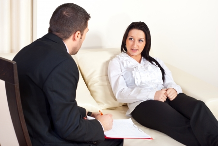Patient woman  sitting on couch and talking with psychologist man  photo