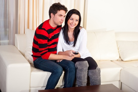 Young couple sitting on sofa home in embrace and watching tv photo