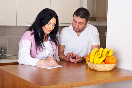 mid adult couple: Serious mid adult couple standing in their kitchen and writing and calculate their expenses Stock Photo