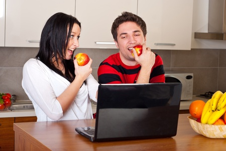 Young couple eating apples having conversation and using laptop in their kitchen photo