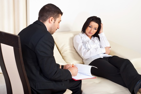 psychotherapy: Psychiatrist talking with depressed woman patient and trying to help  her