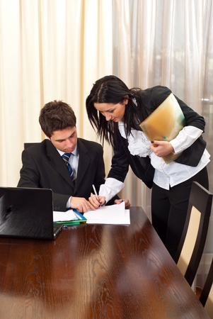 Business woman signing an agreement for other business man partner in a meeting room photo