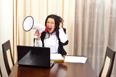 Crazy desperate business woman shouting megaphone and sitting on chair in a meeting room photo