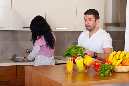 Couple in kitchen preparing food,woman waching vegetables and man holding fresh lettuce photo