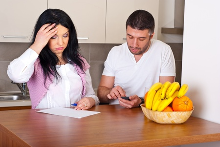 unhappy man: Sad couple having difficult to calculate their expenses