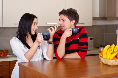 Young couple having conversation and drinking coffee in the morning in their kitchen photo