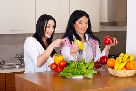 Two women in kitchen having conversation and choice which pepper to use  for salad photo