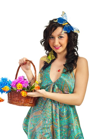 Spring girl with big butterflys in hair showing basket with flowers over isolated on white background photo