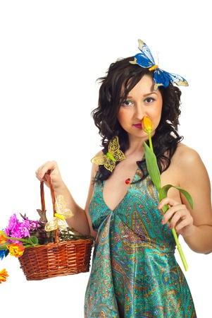 Beauty spring woman model with flowers in basket and buterflys in her hair smelling tulip over white background Stock Photo - 8994101