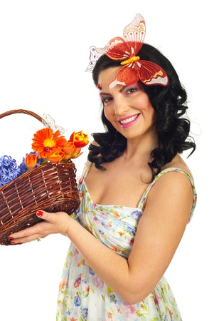 Lovely spring woman holding a basket with fresh flowers and smiling isolated on white background photo