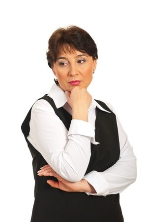 sideways: Worried mature business woman looking sideways and holding hand to chin isolated on white background