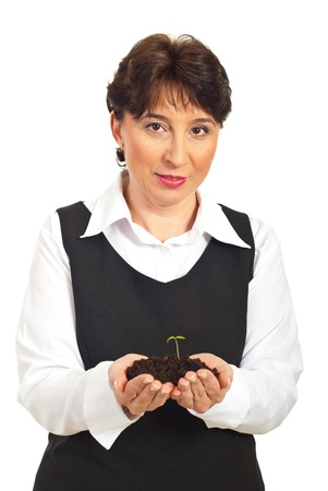 mature corporate woman holding small plant in dirt in her hands isolated on white background Stock Photo - 8990292