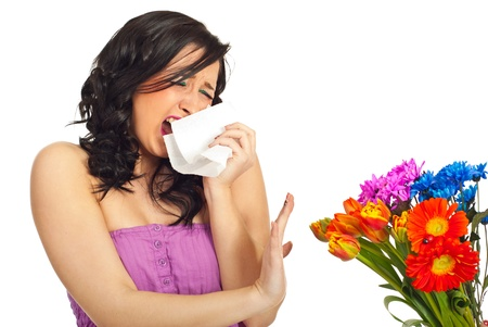with pollen: Young woman sneeze  and trying to stop a spring bouquet of flowers isolated on white background Stock Photo