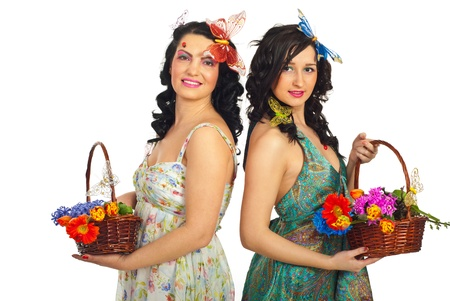 Two beautiful spring women holding baskets with flowers and standing back to back isolated on white background photo