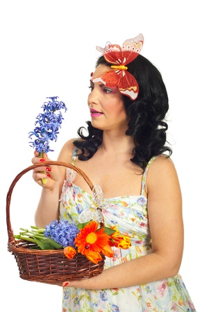Amazed spring woman holding basket with flowers and looking amazed to a violet hyacinth isolated on white background photo