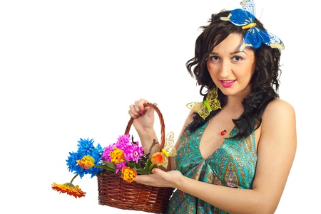 Nice spring girl holding basket with spring flowers against white background photo