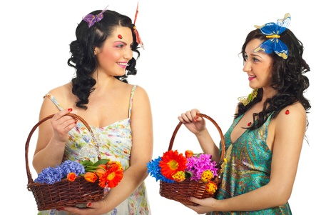 Two beautiful happy women having conversation and holding baskets with flowers over white background photo
