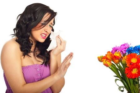 Young woman having spring flowers allergy sneezing and trying to stop flowers over white background photo