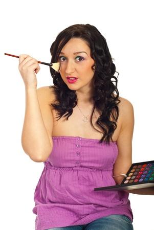 blushing: Amazed girl holding eyes shadow palette and blushing cheek isolated on white background Stock Photo