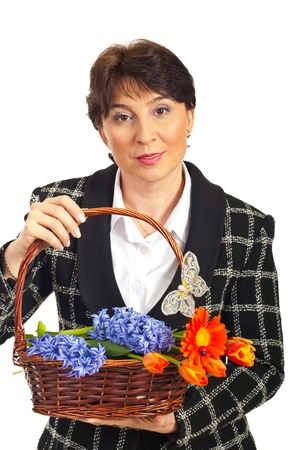 Smiling mature woman holding spring basket with flowers isolate don white background photo