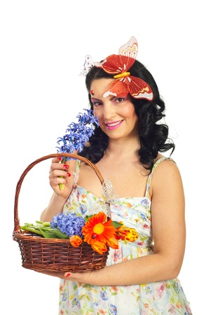 Beautiful spring woman holding basket with flowers and smelling hyacinth isolated on white background photo