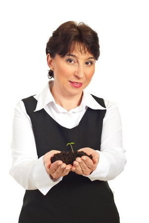 Smiling mature woman holding small plant in dirt isolated on white background photo