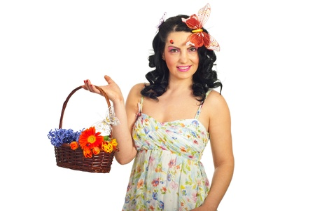 Beautiful spring woman with butterfly in hair holdingbasket with flowers against white background photo