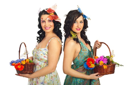 Two beautiful women holding flowers in baskets and standing back to back isolated on white background photo