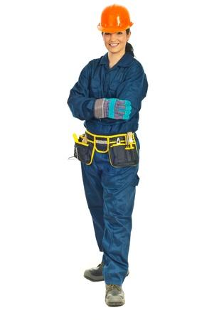 mains crois�es: Toute la longueur du sourire de femme de travailleur constructeur permanent avec les mains crois�es isol� sur fond blanc