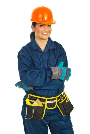 Cheerful builder woman standing with arms folded isolated on white background photo