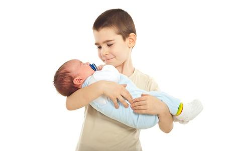 Colegial con su hermano recién nacido aislado sobre fondo blanco Foto de archivo