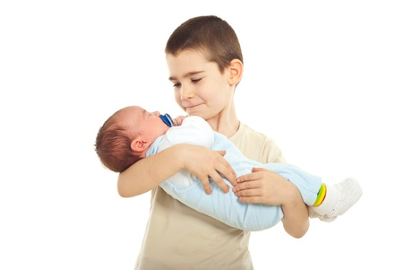 infancy: Schoolboy holding his newborn baby brother isolated on white background