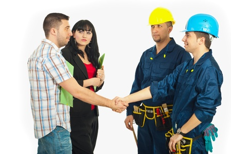 Couple bought a home and giving hand shake with constructor workers team isolated on white background photo