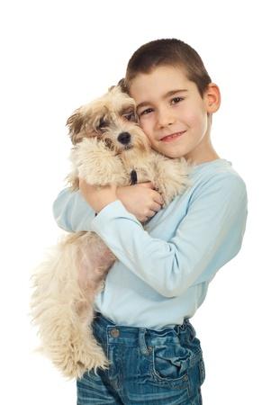 Happy kid boy bonding his puppy dog isolated on white background photo