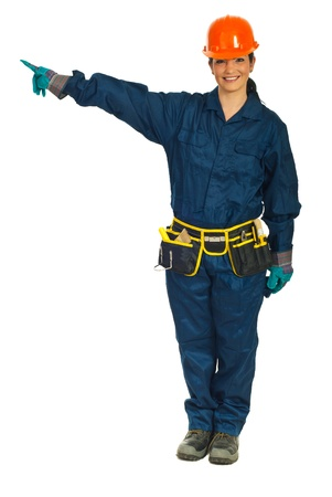Full length of smiling constructor worker woman pointing in left part of image to copy space against white background Stock Photo - 9127993