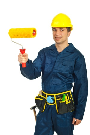 Young painter man in uniform holding paint roller isolated on white background
